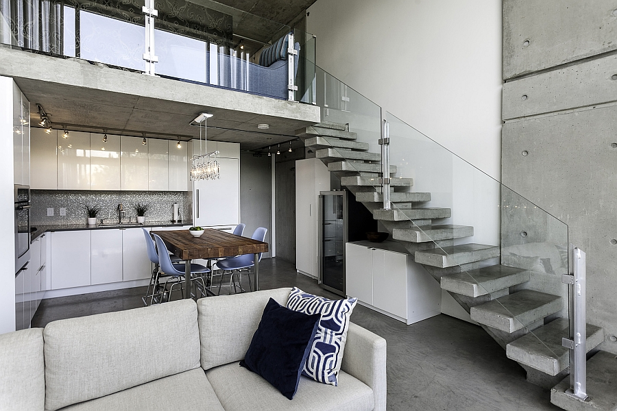 Glass railing for the concrete staircase brings a sense of visual airiness