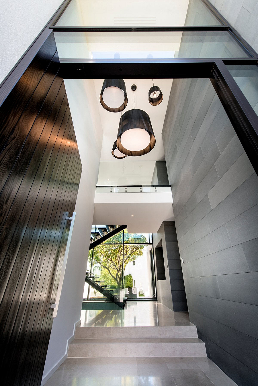 Large pendants hold their own in the hallway with high ceiling