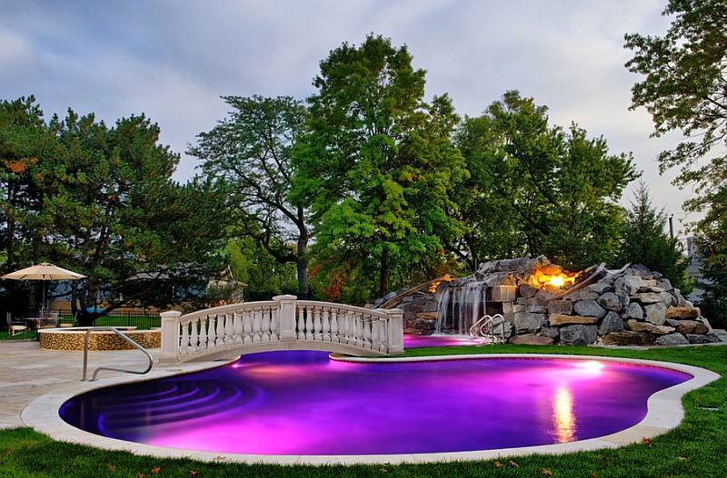 Lighting waterfalls and fireplace shape the stunning poolside landscape