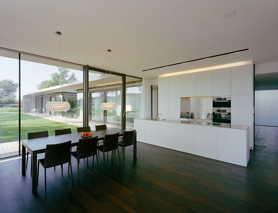 Minimalist kitchen along with sparkling caboche chandeliers above the dining table