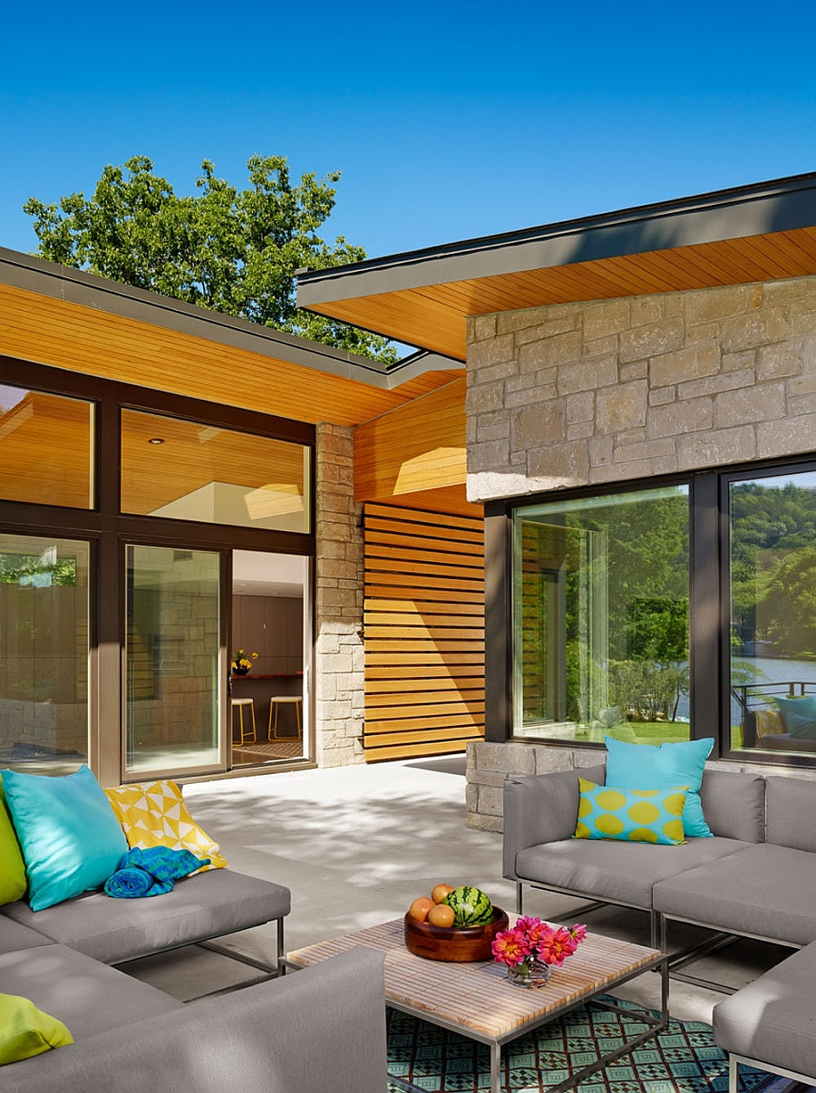 Outdoor lounge with plush sofas in gray and yellow and turquoise accent pillows