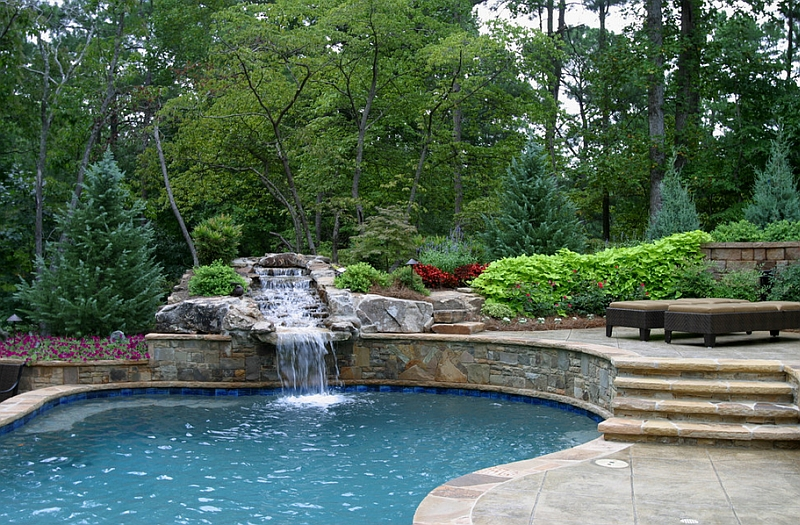Raised patio features a stone waterfall that leads into a pool