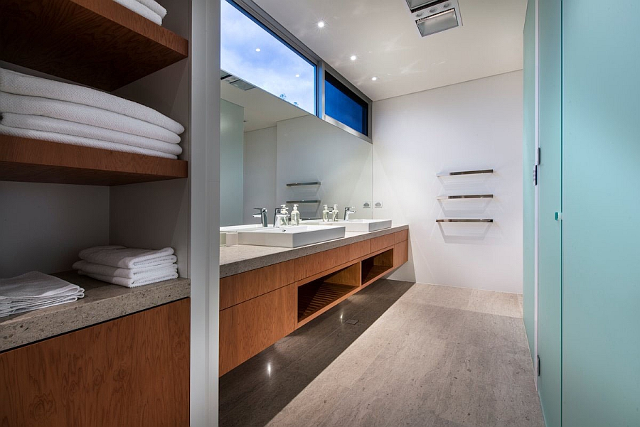 Sleek contemporary bath in white with floating wooden vanity