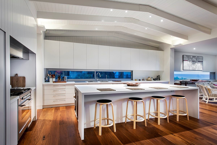 Smart bar stools add visual contrast to the all-white kitchen