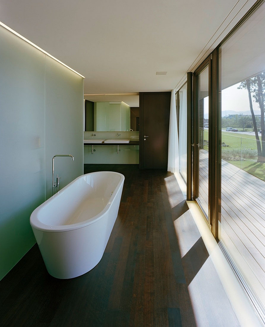 Standalone bathtub in white next to the glass shower area in frosted glass