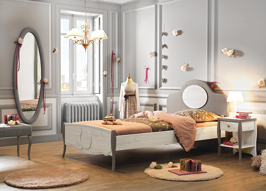 Wall-mounted oval mirror adds to the timeless look of the elegant girls' bedroom