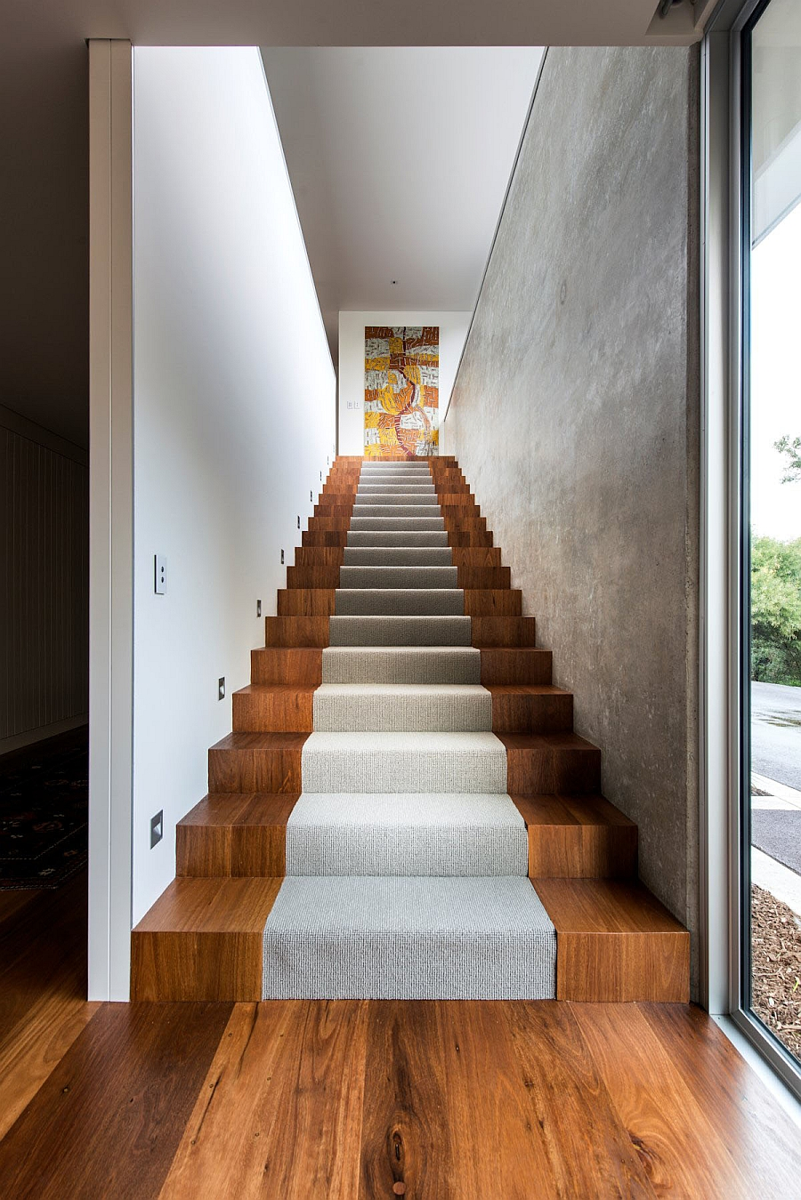 Wooden staircase flanked by concrete walls leads to the top level