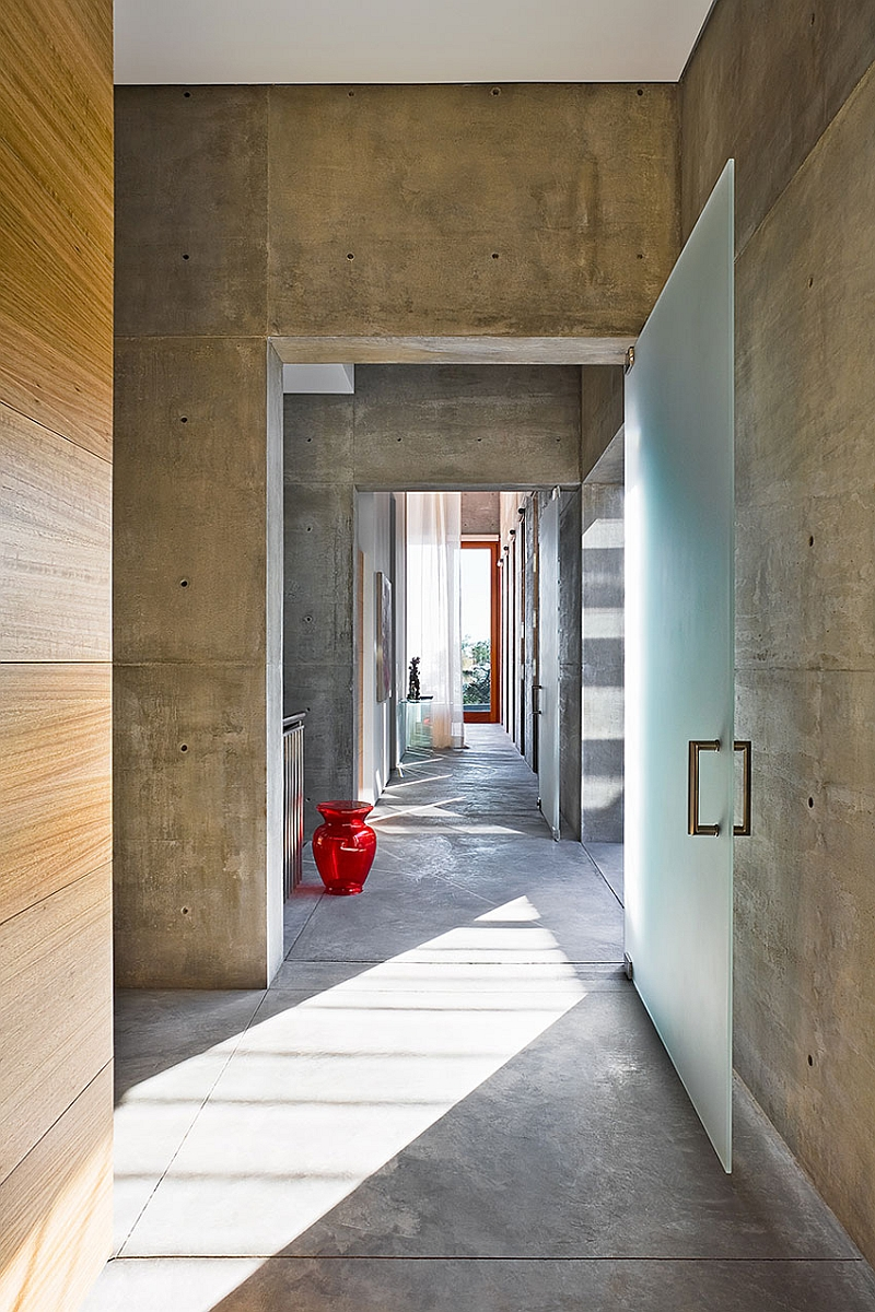 An entry way that is smart combination of natural wood, glass and concrete