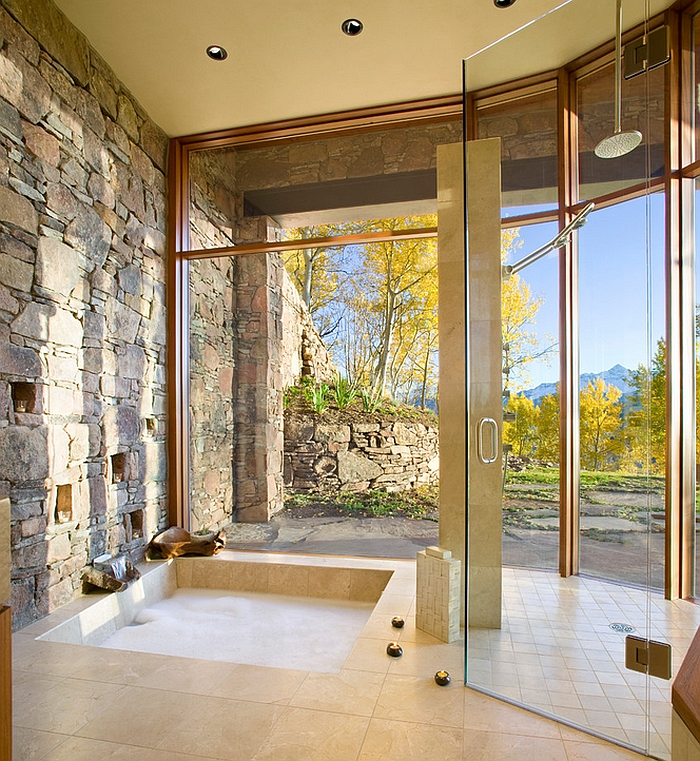 Bathroom with a natural stone wall, marble floor and sunken tub