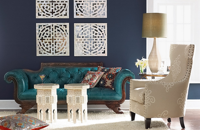 Beautiful teal chaise lounge placed in a living room with navy blue walls
