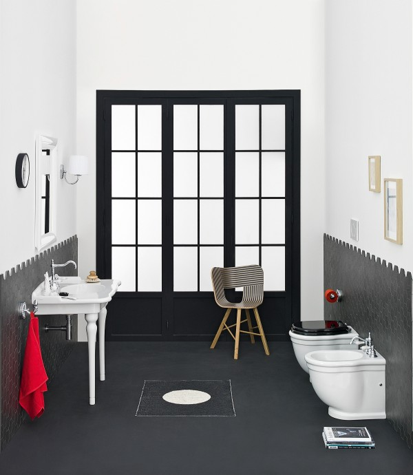 Black framed door adds drama to the bathroom while pops of red enliven it with ease