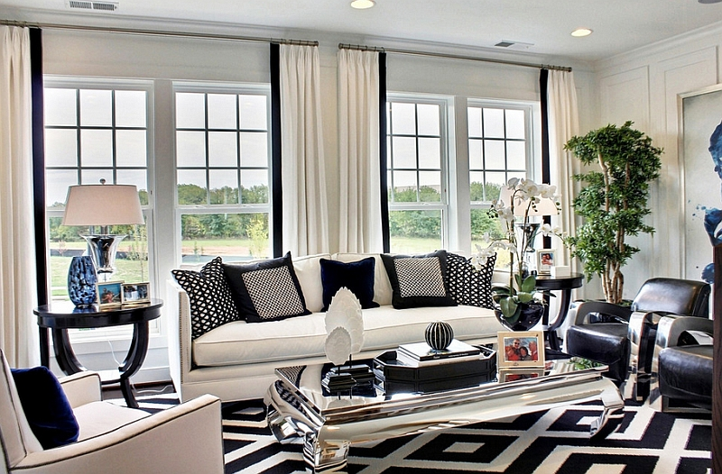 Bold pattern of the rug and the throw pillows drive home the black and white color palette Black And White Living Rooms: Charismatic Style And Timeless Elegance!