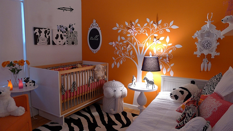 Brilliant use of orange along with black and white rug in the nursery