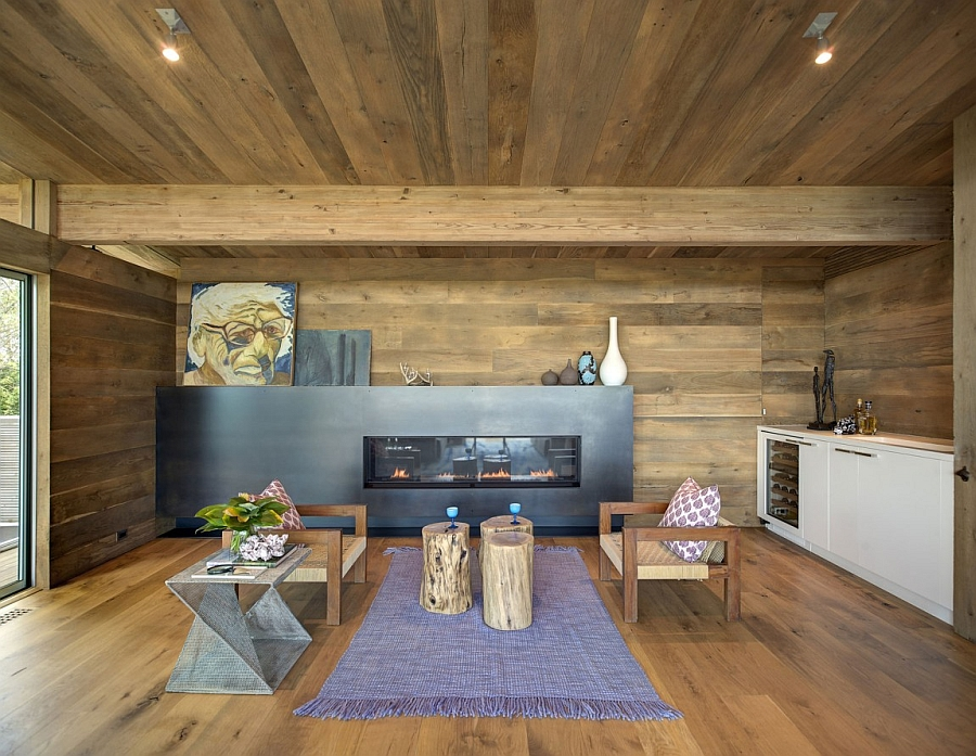 Cozy family room with a sleek fireplace and walls and ceiling with wood paneling