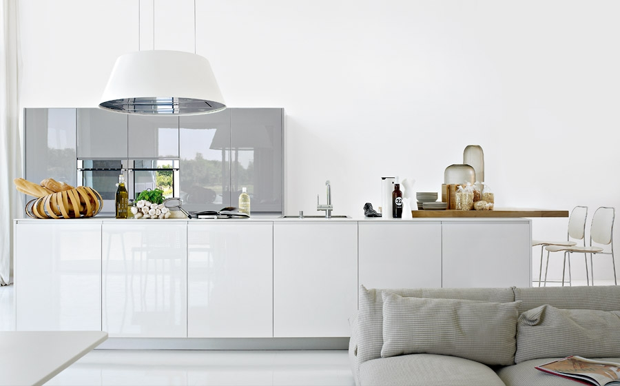 Dramatic pendant light and smart wooden surfaces add intrigue to the glossy kitchen