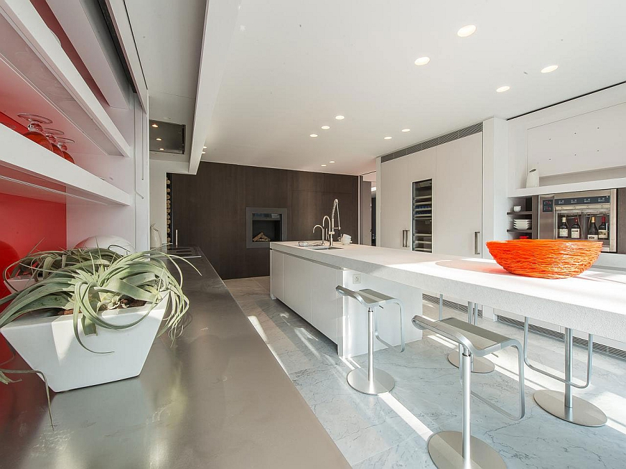 Expansive kitchen island, stainless steel countertops and wooden accent wall shape the stylish kitchen