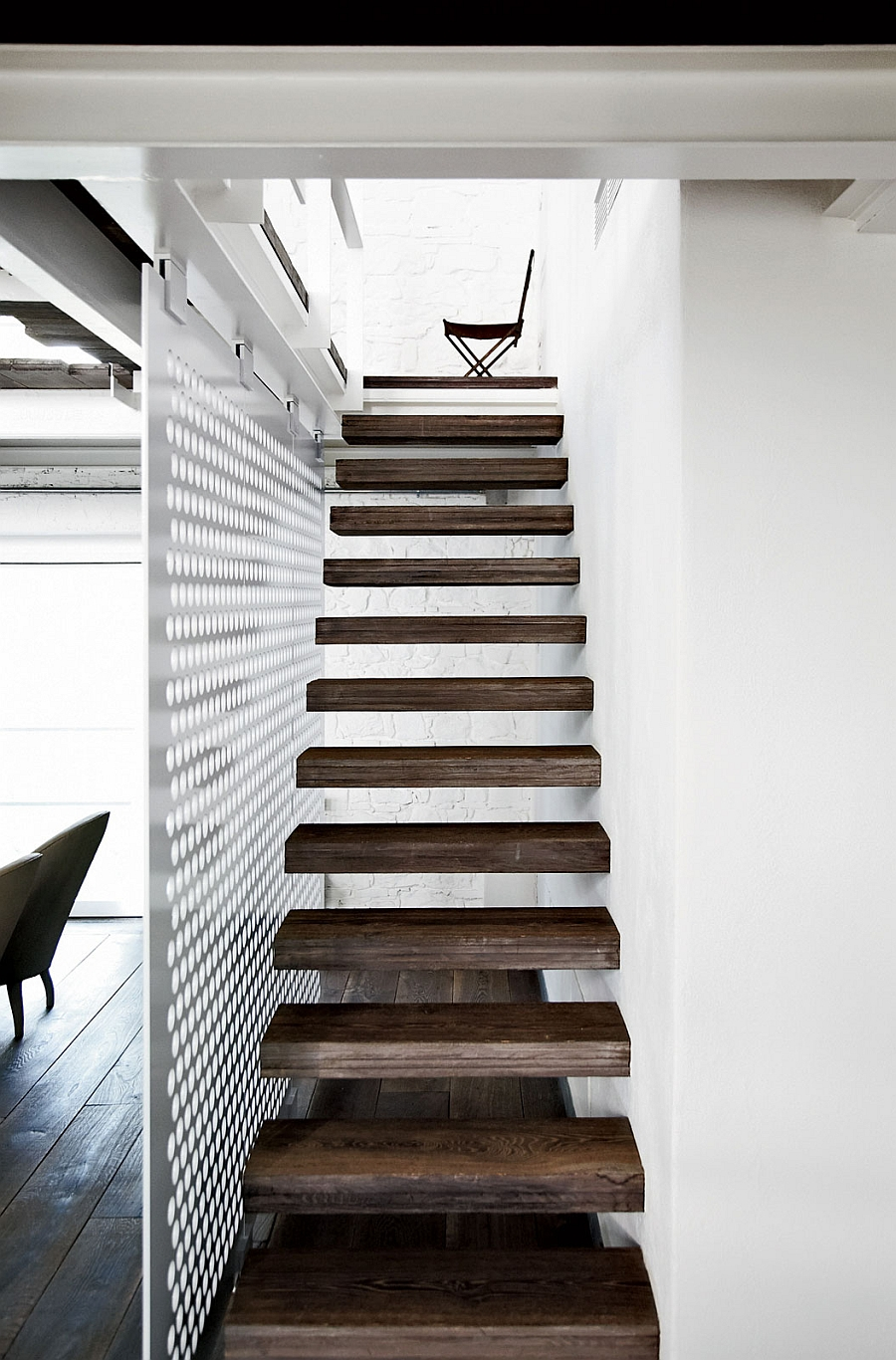 Floating wooden staircase standsout visually thanks to the white backdrop