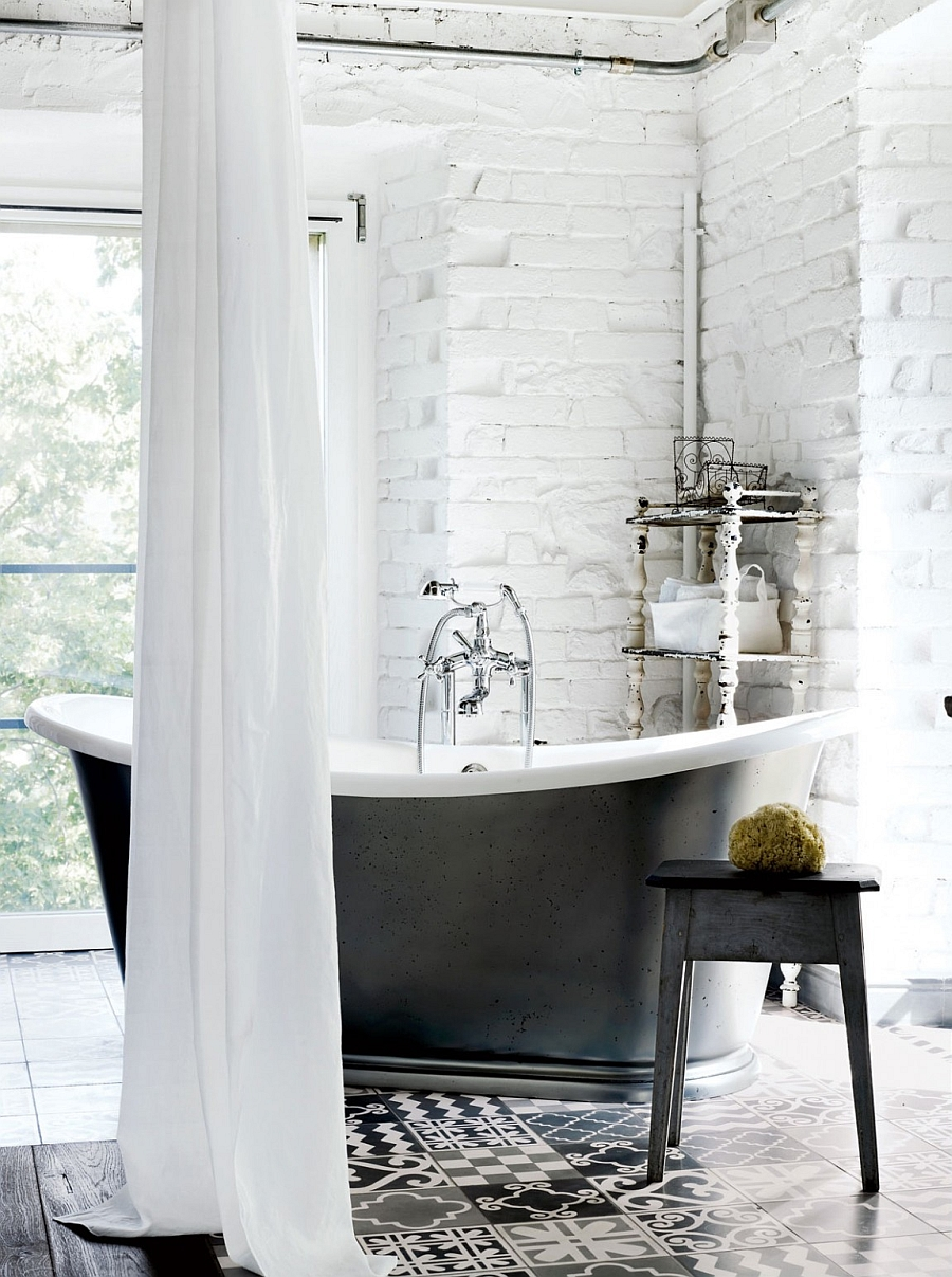 Freestanding bathtub in black set against a white brick wall in the relaxing bath