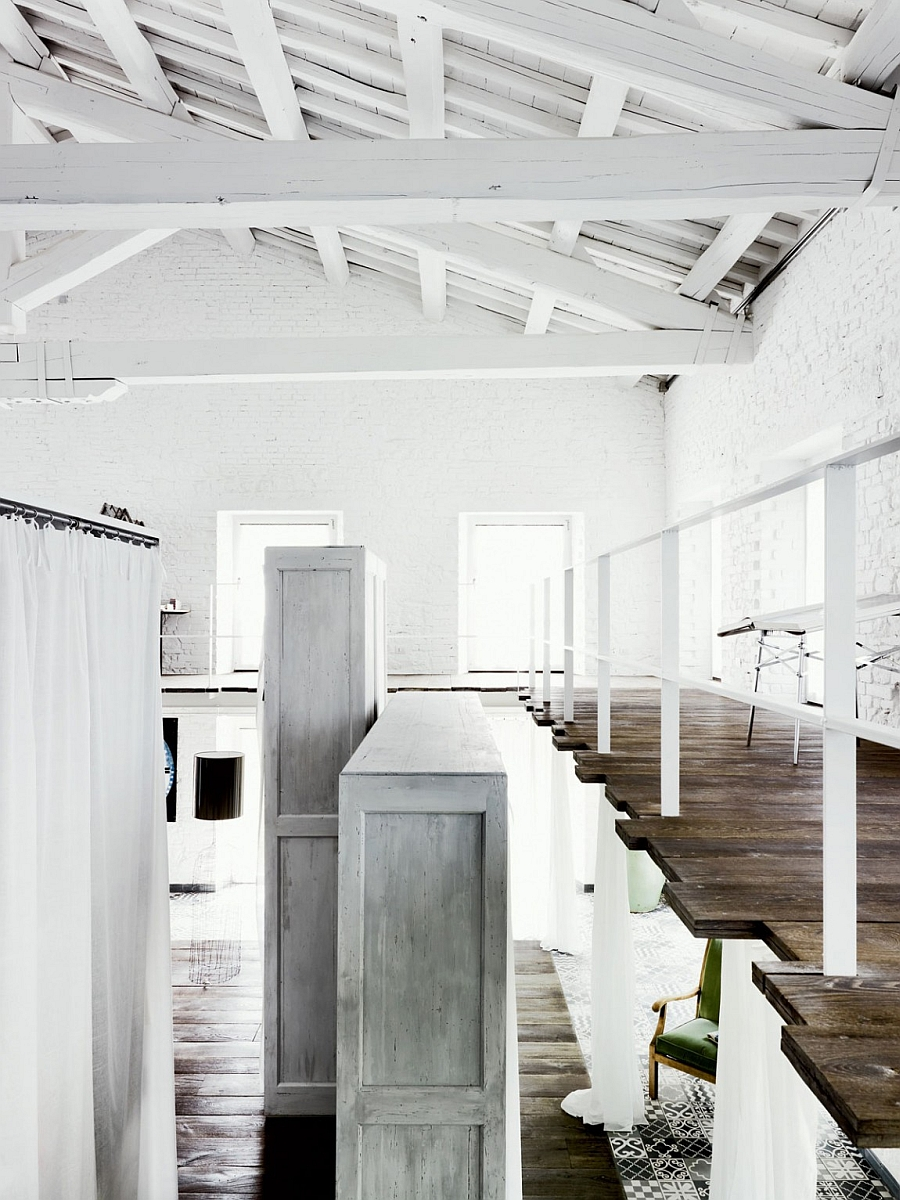 High ceiling with exposed and painted wooden beams and mezzanine level inside the industrial home