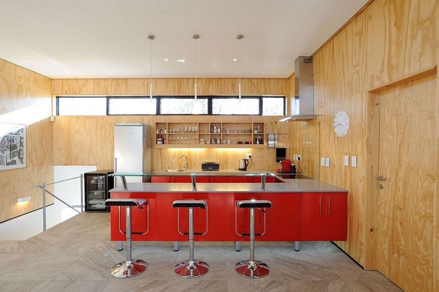 LEM Piston bar stools and a ravishing red kitchen peninsula enliven the space