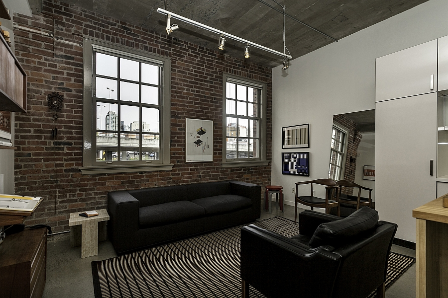 Living area of the loft with brick walls and plush decor