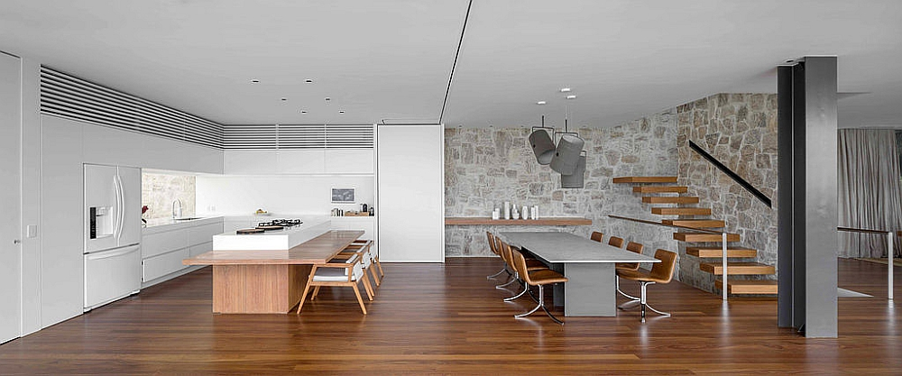 Modern dining room and kitchen with a stone backdrop