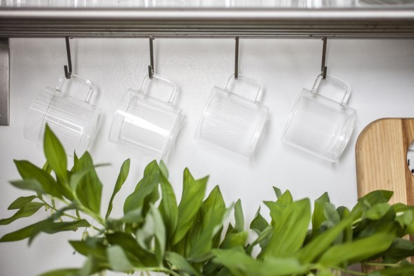 Mugs hang from a stainless steel shelf