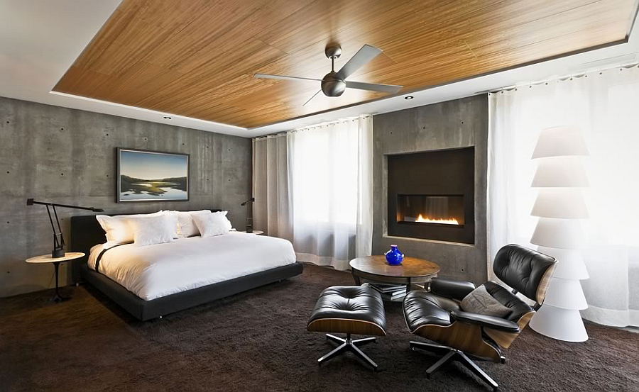 Natural eucalyptus ceiling in the bedroom with exposed concrete walls and the iconic Eames Lounger