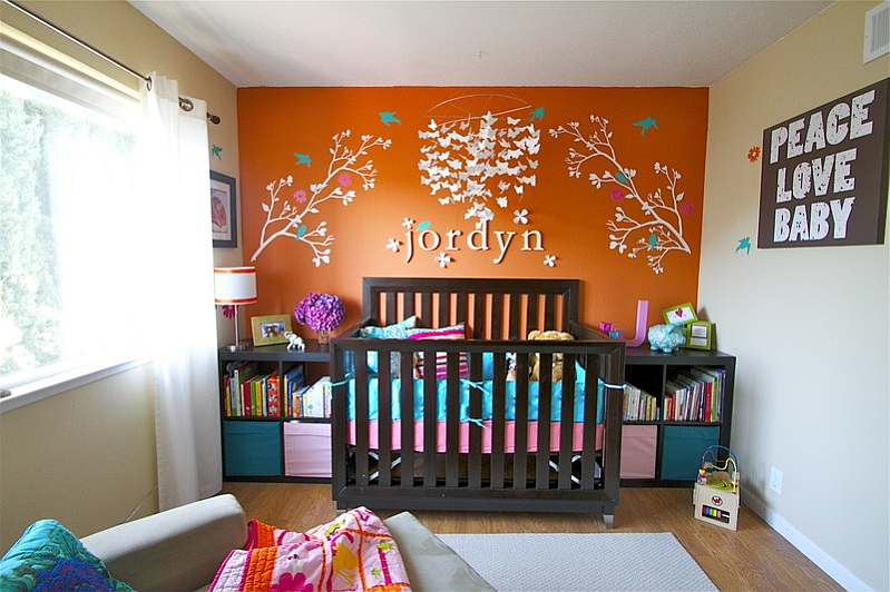 Orange accent wall in the small nursery steals the show