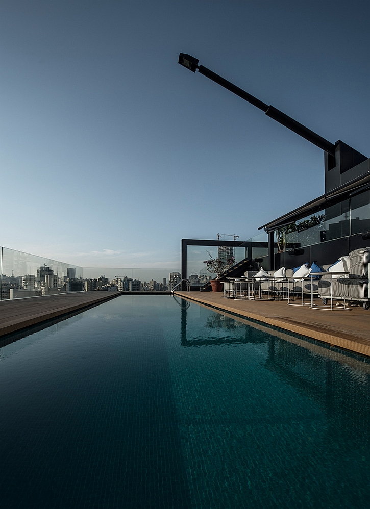 Outdoor terrace pool with two unique antenna style light fixtures above Elite Penthouse Apartment Astonishes With Its Stunning, Steely Design