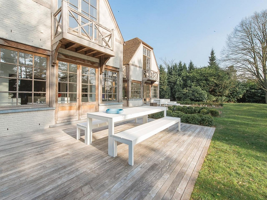Outdoor wooden deck with cool dining space extending into the lavish backyard