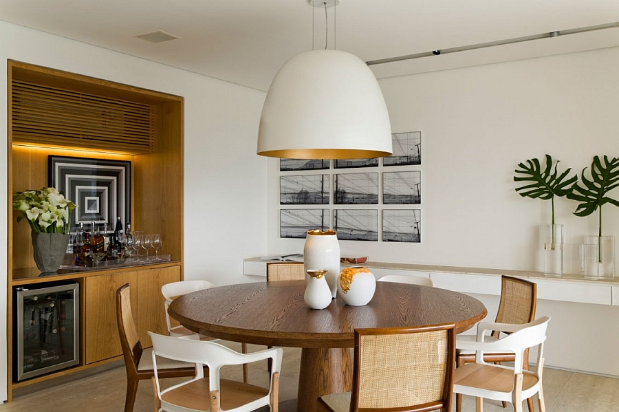 Oversized pendant above the dining table with a glint of golden yellow