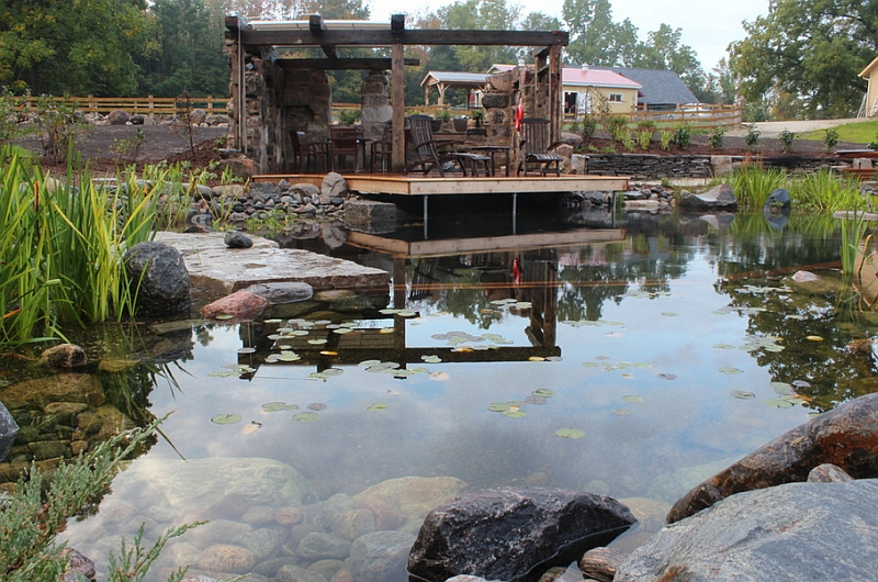 Rustic natural pool with a farm backdrop and a faux ruin shelter!