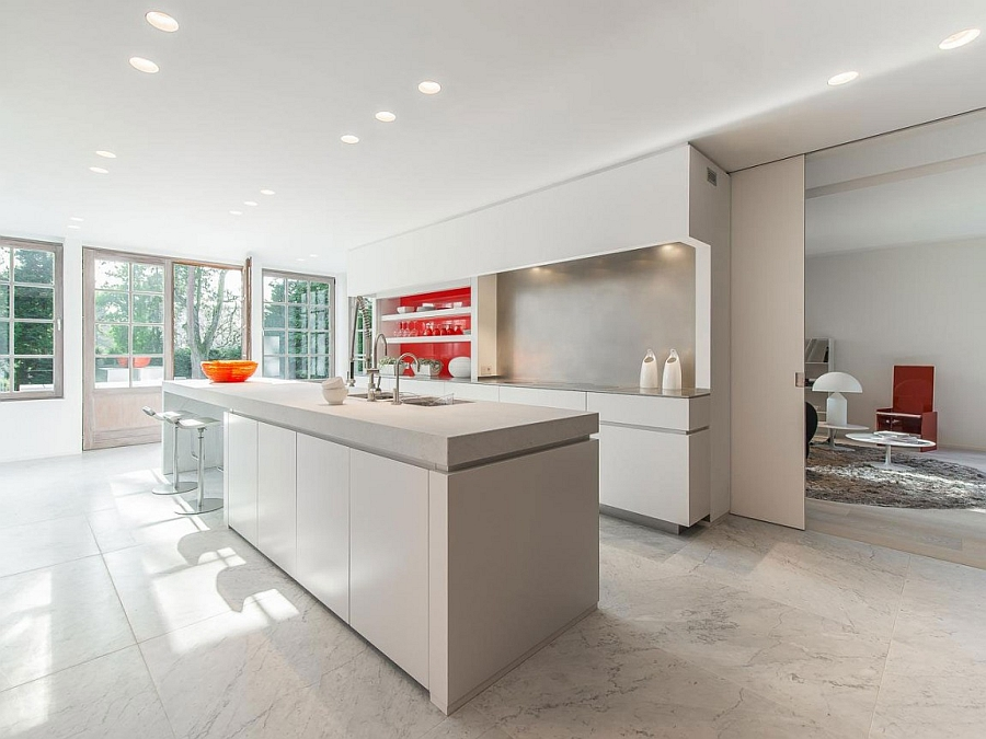 Sleek and spacious modern kitchen in white with a hint of red