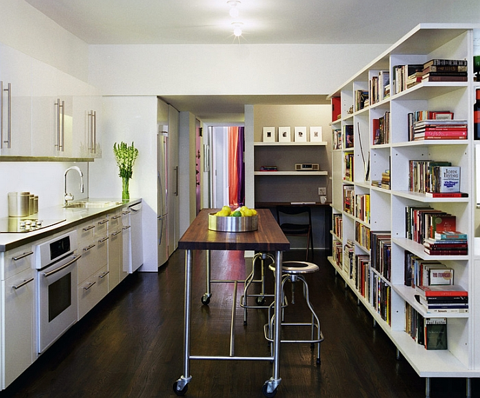 Sleek kitchen island on wheels occupies the slot between the counter and the bookshelf