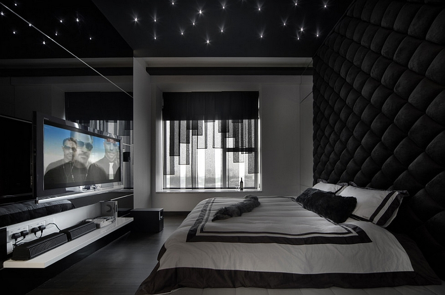 Stunning bedroom in black with tufted wall, ceiling LED inserts and an expansive entertainment unit