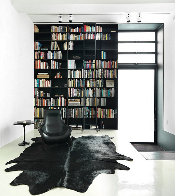 Uber-stylish blacka nd white living room with a giant bookshelf that defines the space