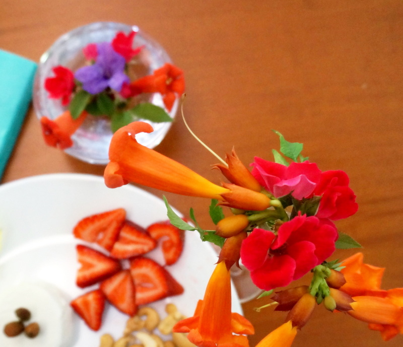 Blossoms in glass vases surround a food plate