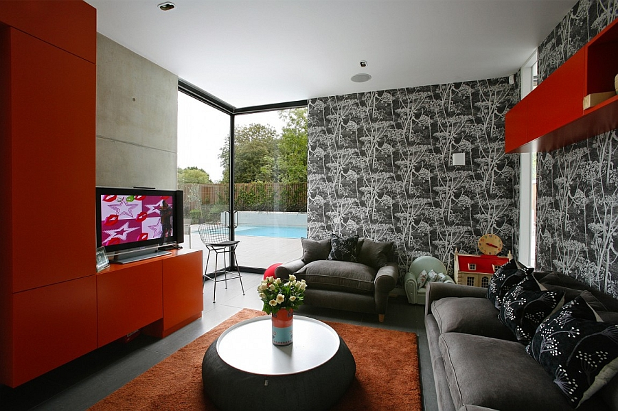 Bold red shelves and wallpaper add style to the sitting room