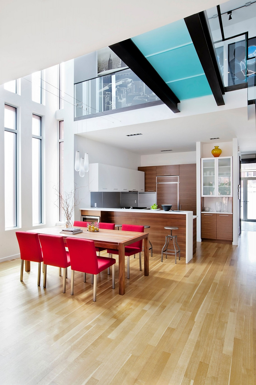 Dining table chairs add bright pops of red to the trendy interior