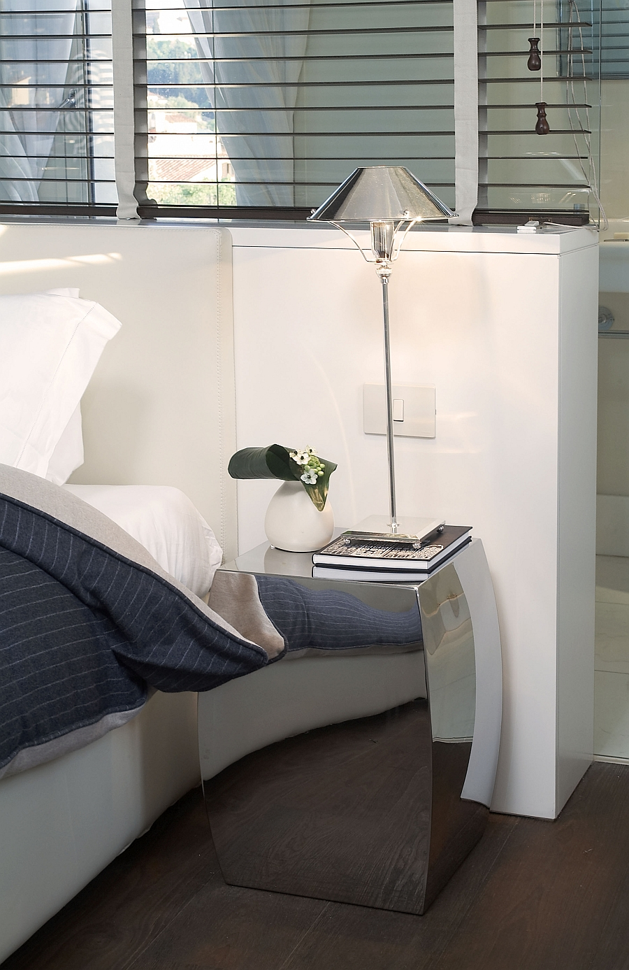 Flashy nightstand adds a cool reflective surface to the small bedroom