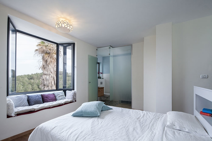 Master bedroom with an en shiute bathroom and window niche that offers scenic views