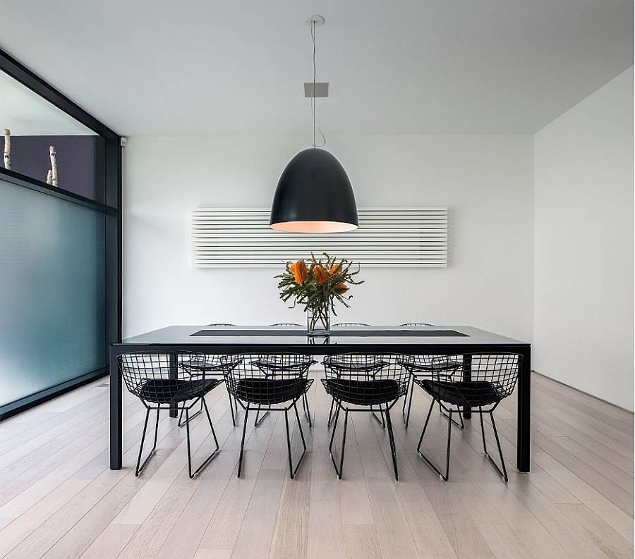 Oversized pendant light iluuminates the sleek, minimal dining space
