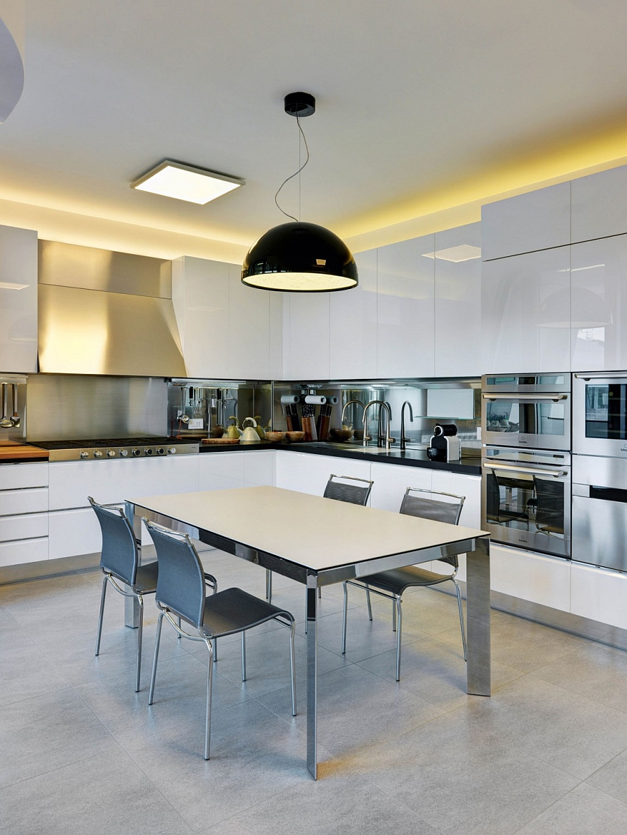 Oversized pendant light in black becomes the focal point of this sleek, white kitchen