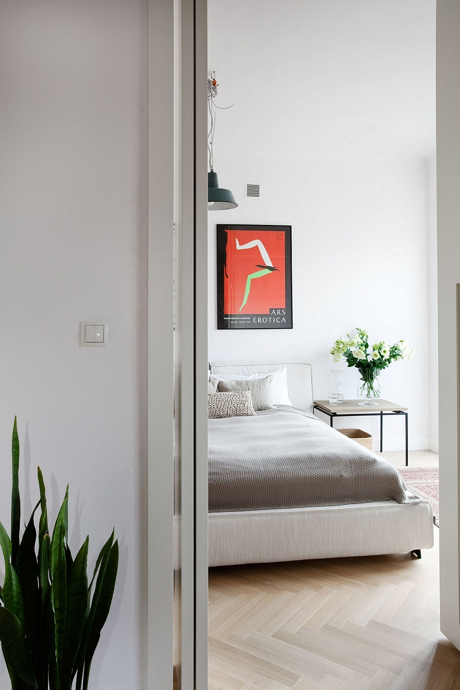 Smart side table and flowers add natural zest to the serene bedroom