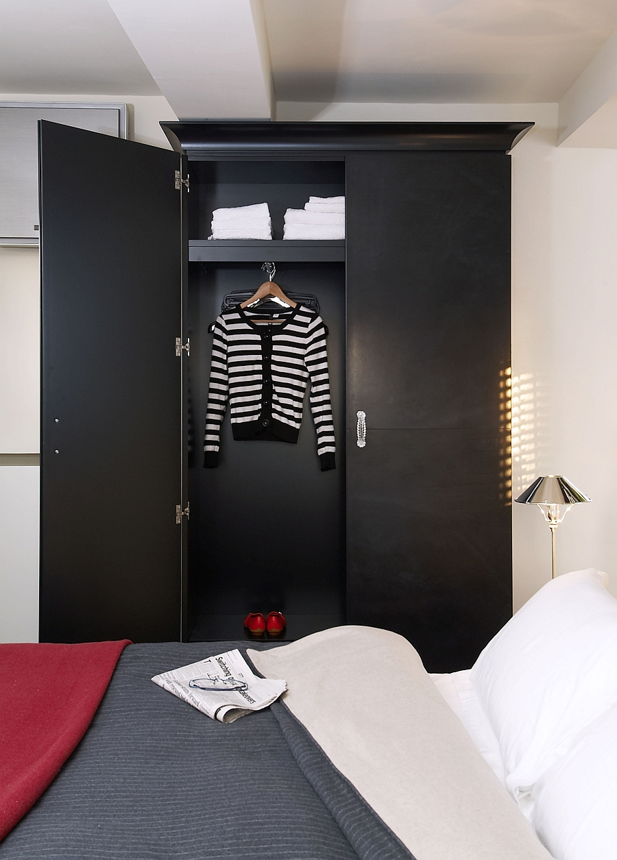 The wardrobe in black brings visual contrast to the room