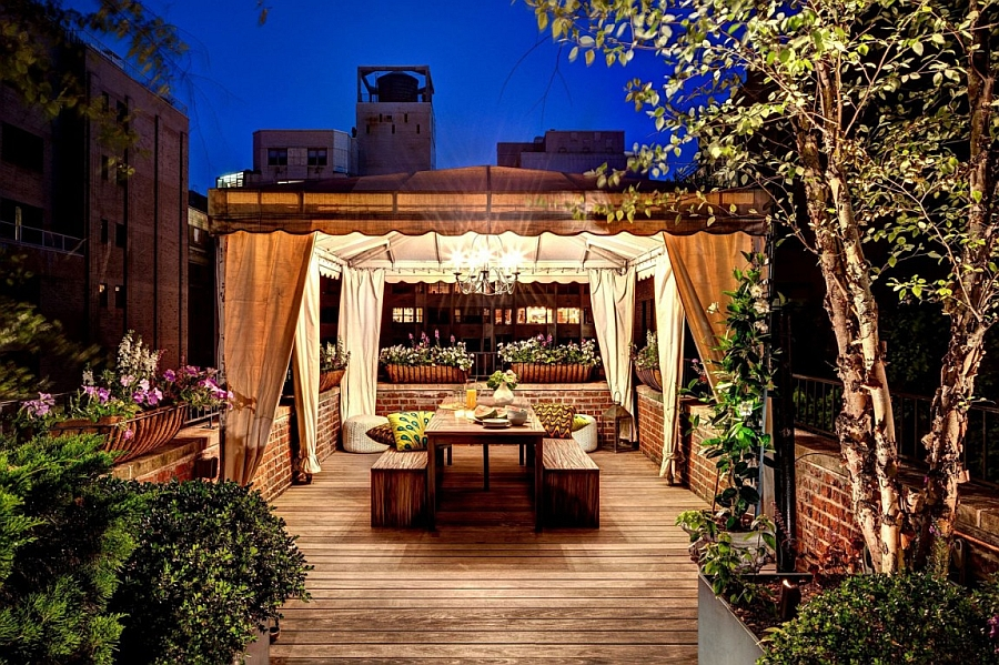 An outdoor dining space nestled among natural greenery of the rooftop garden