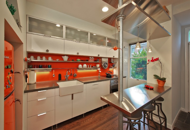 Stainless steel shelving pops against a vibrant orange wall