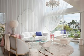 White drapes and cozy decor give the spacious room a trendy, feminine look [Design: BNO]