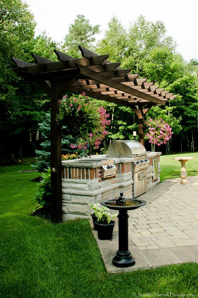 An idyllic backdrop for the beautiful outdoor kitchen [Design: Forest Ridge Landscaping]